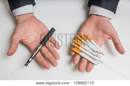 Hands Are Holding Electronic And Conventional Tobacco Cigarettes