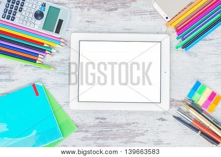 back to school hero header with school supplies on wooden table, copy space on blank screen of tablet