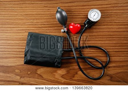 Tonometer with red heart on wooden table