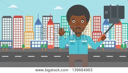 An african-american man making selfie with a selfie-stick. Man taking photo with cellphone and waving on a city background. Vector flat design illustration. Horizontal layout.