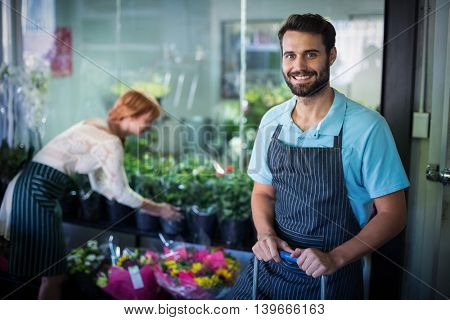 Male florist standing while female florist working in the background at flower shop