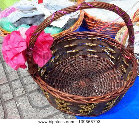 medium-sized round wicker basket with handle lightly wrapped with a thin, pink ribbon, crepe flower tied on lower left side of handle, with other baskets on sidewalk and blue tarp, Songkhla market, Thailand
