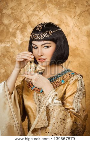 Young girl with perfume bottle. Glamorous closeup portrait of beautiful sexy stylish brunette young woman model with bright makeup with gold jewelery. Cleopatra poster