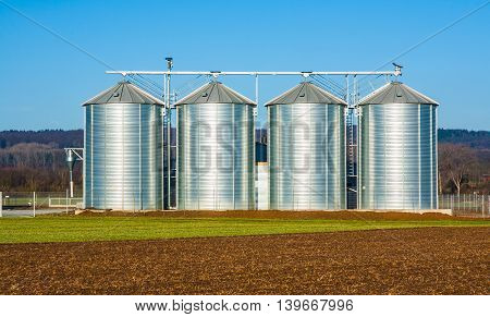 silver silo in rural landscape under blue sky