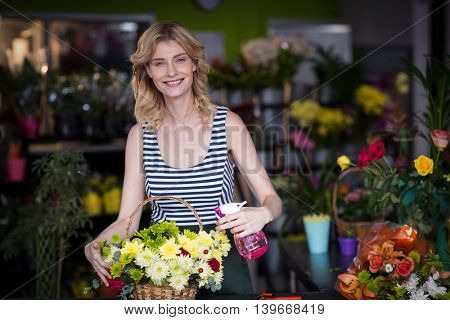 Portrait of smiling female florist spraying water on flowers in flower shop