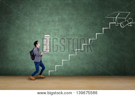 Male college student carrying a pile of book with stairs on the blackboard