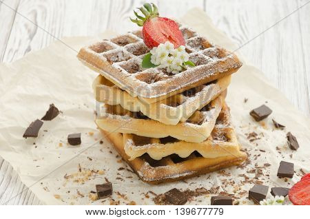 Homemade baking. Viennese waffles with powdered sugar chocolate strawberry on wrapping paper.