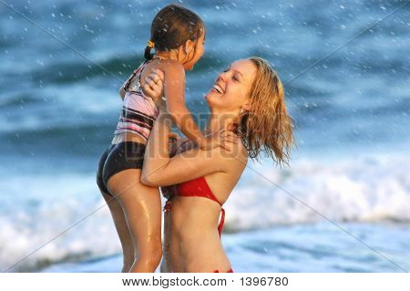 Mother And Daughter Playing In The Ocean