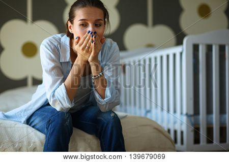 Young tired woman sitting on the bed near children's cot.