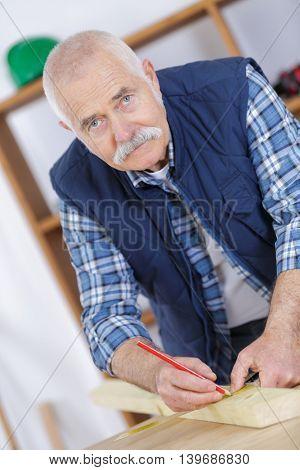 senior carpenter marking woodboard in workshop