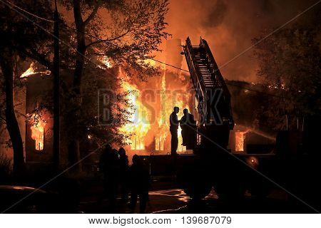 two silhouettes on fire truck on housefire background