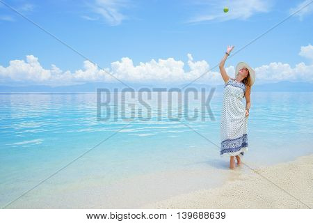 Young europian woman in light dress and hat walking on white sand beach near calm amazing sea and playing with green apple at sunny day under blue cloudy sky.