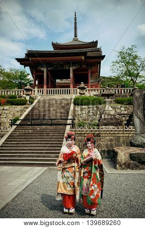 KYOTO, JAPAN - MAY 18: Geisha stand in Shrine on May 18, 2013 in Kyoto. Former imperial capital of Japan for more than one thousand years, it has the name of City of Ten Thousand Shrines.