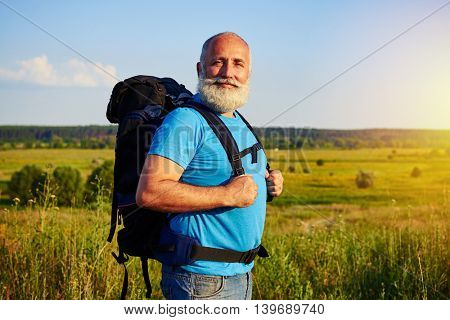 Active fit aged tourist with white beard is standing with rucksack behind his back against sunlit field background