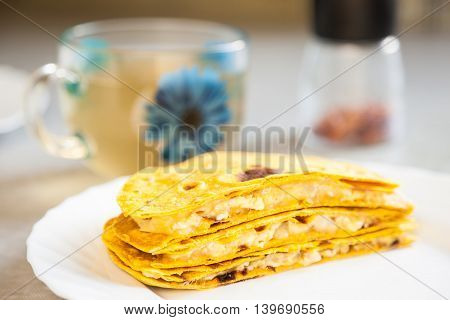 Delicious quesadillas with crispy corn tortillas on a white plate. A traditional Mexican meal. Beautiful bokeh very shallow depth of field