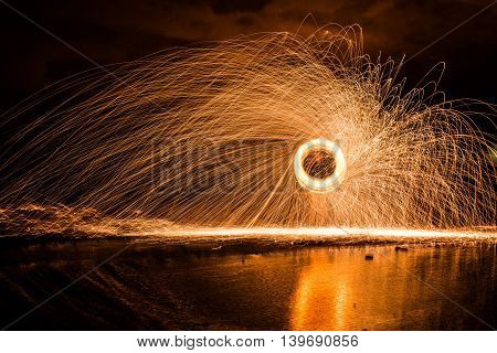 Spinning Steel Wool Sparks over Reflecting Pool of Water