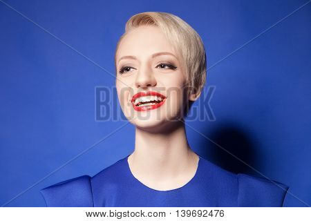 Studio shot of pretty and candid girl with short hair in blue laughing while looking away