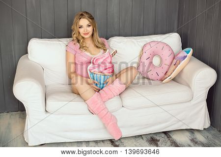 Beautiful pregnant woman looking at camera and smiling sitting on a couch. The happiest time for every woman. Ice cream and doughnut in the hands of a pregnant girl