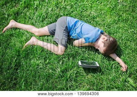 boy fell asleep on the grass with tablet. child sleeping on the grass under the sun after a play on the digital tablet. view from above
