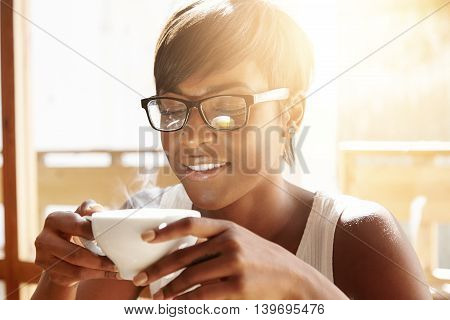 People, Drinks And Leisure Concept: Happy Dark-skinned Woman Wearing Glasses, Drinking Tea From Cup