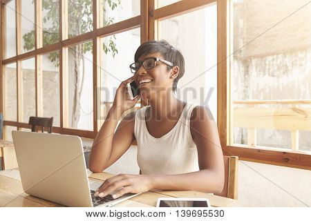 Cute African Female Student With Short Stylish Haircut Sitting At A Cafeteria Shopping Online Using