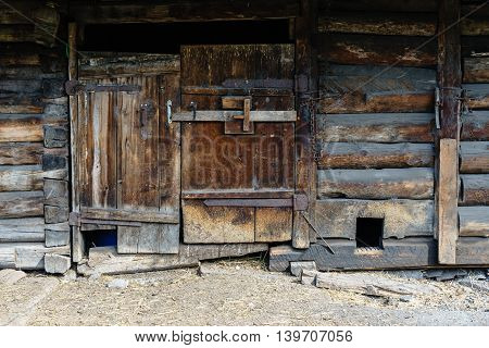 Rustic wooden house doors and shutters kennel for the dog logs and planks beams locking door dust dirt hay. The stable enclosure for livestock.