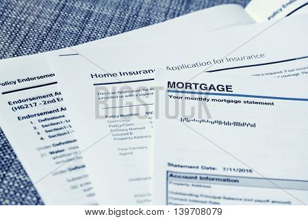 Monthly mortgage statement with home insurance policy papers