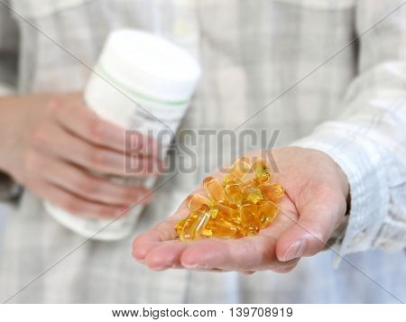 Lady with nutritional supplement pills in hand