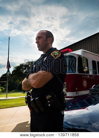 Police officer standing proud with fire truck in background
