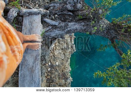 Highly Detailed Photo Woman Legs. Girl Looking Down Cliff Old Tree. Blue Ocean Water Blurred Background.Horizontal picture. Top View