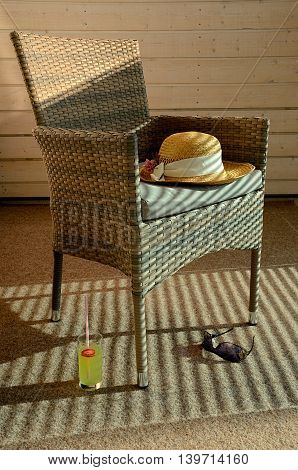 Hot day on the terrace. Sunhat, shades and beverage on the terrace on semi-shade.