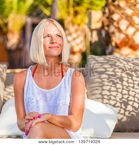 Amazing sensual seductive woman siting on deckchair, enjoying summer holidays near the pool against the background of palm trees.
