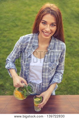 Portrait of beautiful young girl pouring lemonade looking at camera and smiling while standing outdoors