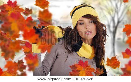 Schöne Frau mit Hut und Handschuhe und Ahorn-Blätter