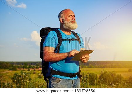 Fit handsome bearded man with rucksack and data tablet against sunset field background
