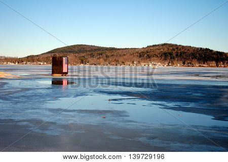 A lone ice fishing shelter sits on a frozen lake.