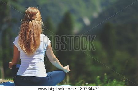 woman doing yoga meditating in the lotus position with his back to nature in the summer