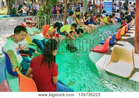 Ho Chi Minh city ( Saigon ) Vietnam - September 02 2015: People have feet fish massage in children water park and historical theme amusement park Suoi Tien - popular travel destination in Vietnam.