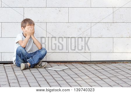 Child tired sad stressed with tablet computer PC. Boy sitting on the ground, holding his head, close eyes. Casual wear. Outdoor. Education, learning, technology, addiction concept