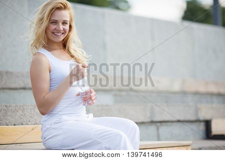 Blonde girl in white dress sitting on bench and holding a bottle of water. Symbol of healthy lifestyle and freshness