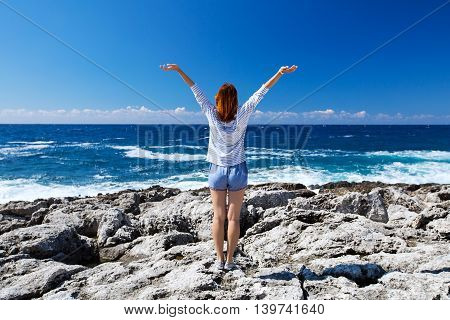 Young Woman With Arms Raised At The Beach