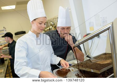 chef and assistant prepare chocolate fill for pastries