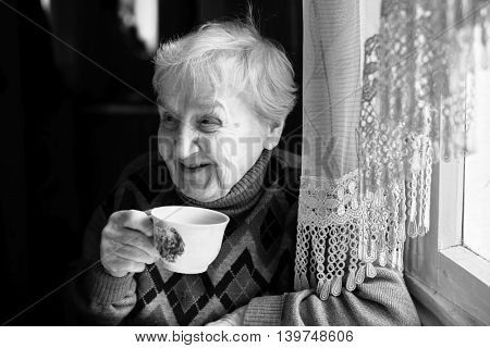 Elderly woman drinking tea. Black and white photo.