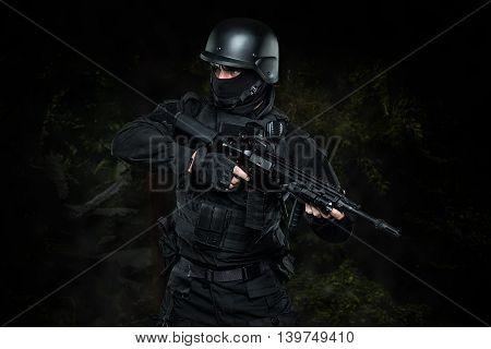Spec ops police officer SWAT in black uniform studio