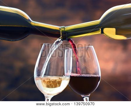 Red and white wine pouring in glass on brown background