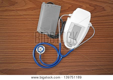 Stethoscope and tonometer on wooden table