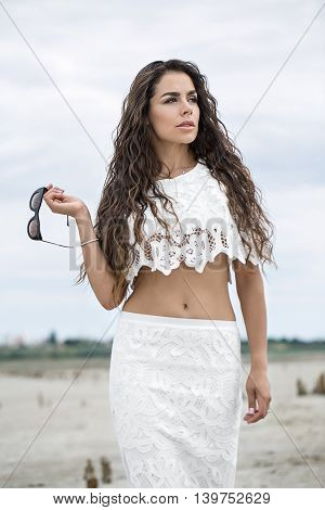 Sexy girl stands on the sand on the cloudy sky background. She wears a white lacy top and a white lacy skirt. She holds sunglasses in the right hand, which bend in the elbow, left hand is along the body. She looks to the side with parted lips. Outdoors. V