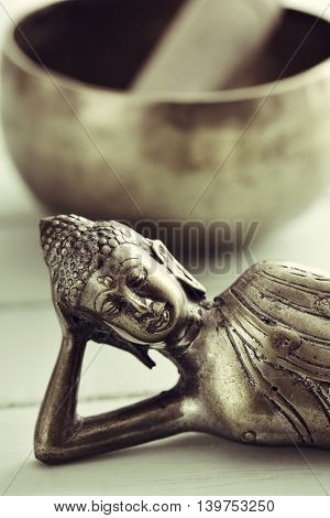closeup of a representation of the buddha laying down, on a pale green rustic background, and a singing bowl with its mallet in the background