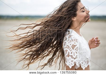 Portrait of a beautiful brunette in a white lace dress. Girl walking on sandy estuary looked like a desert.