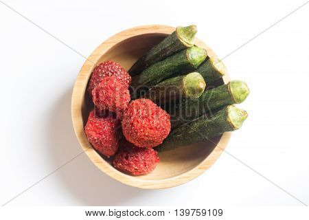 Okra chips and crispy strawberry in wooden bowl stock photo